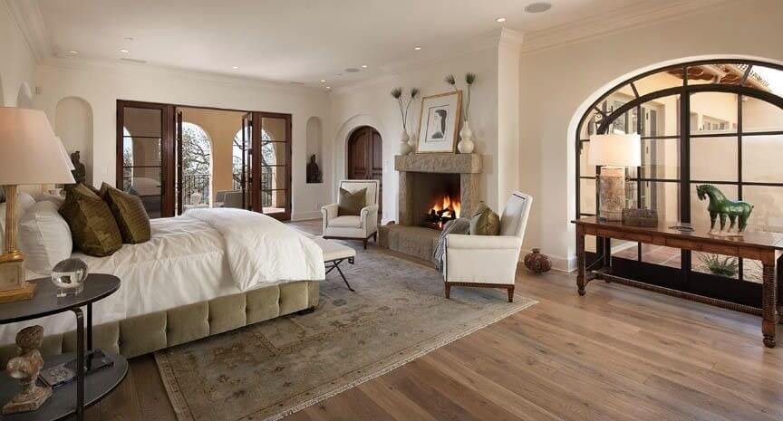 light hardwood floors are covered by a beige patterned rug an arched