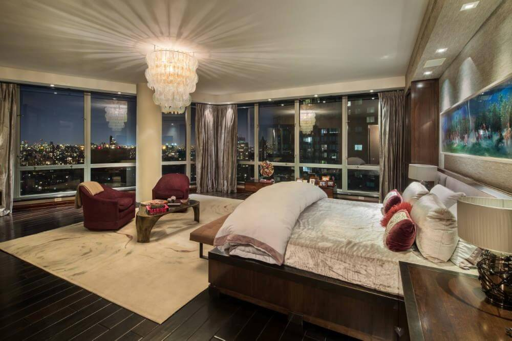 Swanky chandelier hangs above red chairs and natural wood coffee table   Velvet bedding and rug. 38 Gorgeous Master Bedrooms with Hardwood Floors