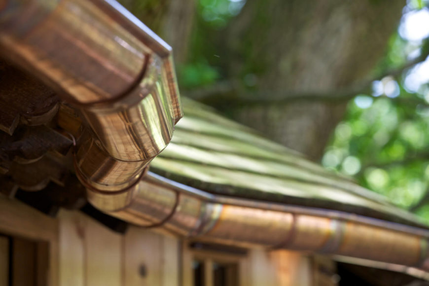 A close-up of the roof and copper drainage pipes.