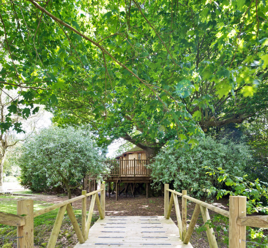 A small, rustic wooden footbridge leads from the family home to the treehouse.