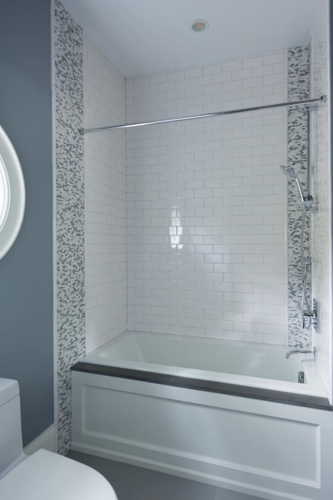 Traditional shower and bath stands inside white tile brick space, flanked by patterned micro tile strips.
