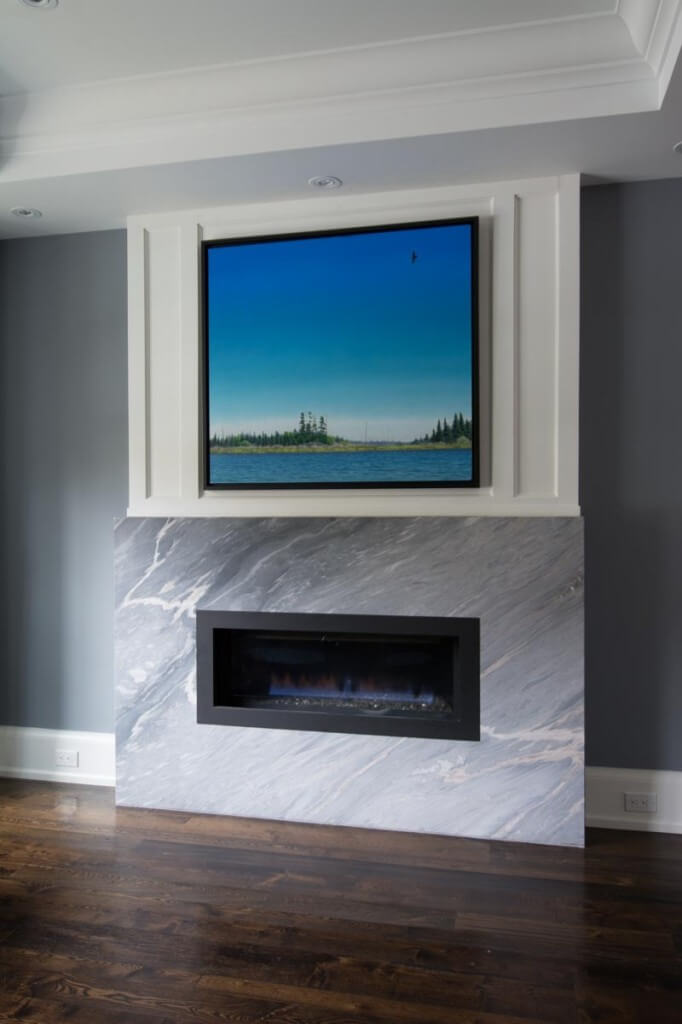 This secondary, gas fireplace in a marble frame stands above a rich hardwood floor, with white wood framed painting above.