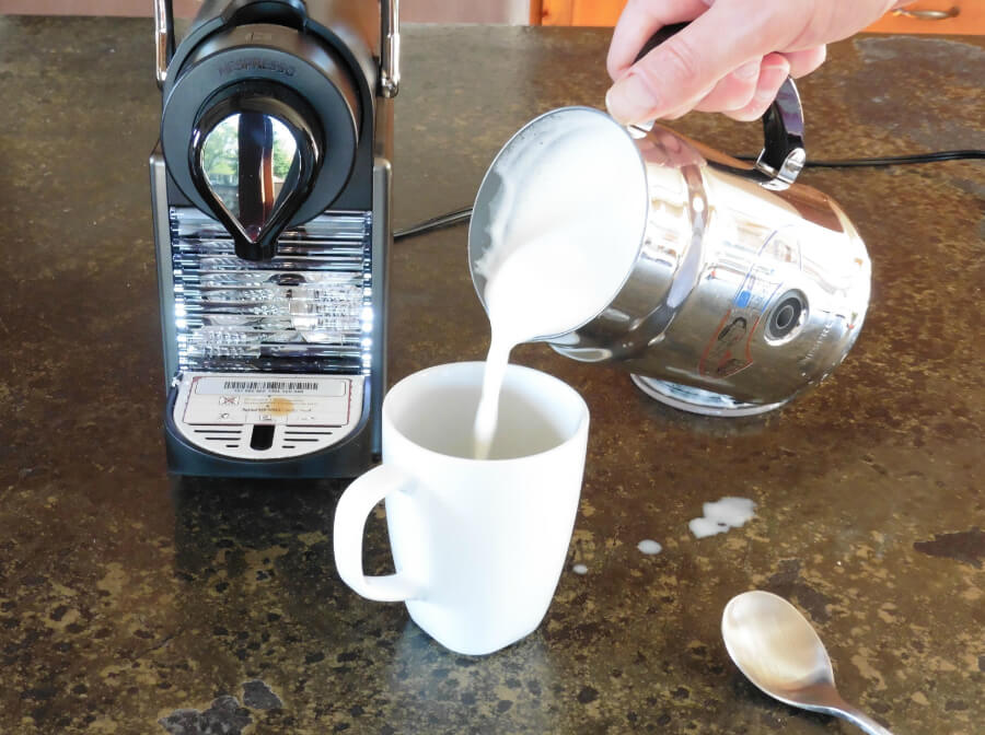 Pouring warm milk from the Aeroccino Plus Milk Frothing Machine