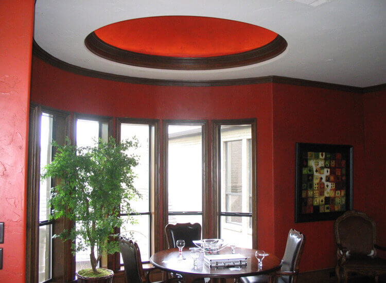 bright red dome above the rich wood dining set echoes the red walls ...