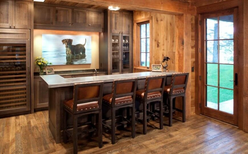 This full bar space features metallic countertop over rich dark wood cabinetry, with  a full height wine cooler built in at left. Leather cushioned bar stools stand next to glass patio door.