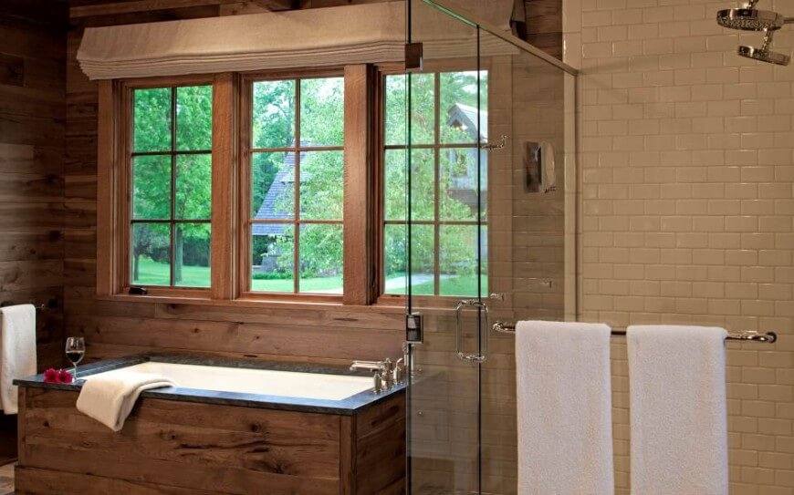 Beside the shower, we see this marble topped, wood frame soaking tub below a trio of windows.