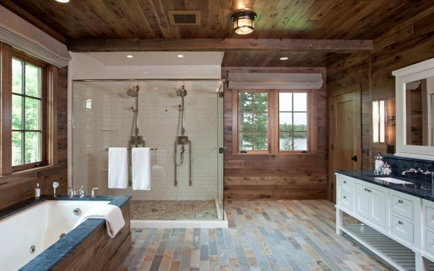 The bathroom holds an immense glass enclosed shower, with white tiling walls and mosaic floor surface. Dual rainfall shower heads add function for two in the large space.