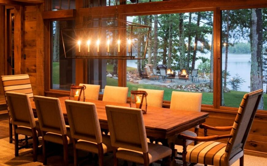 The dining room seen with candle illumination, revealing expansive views toward the independent patio space near the lake through massive natural wood framed windows.