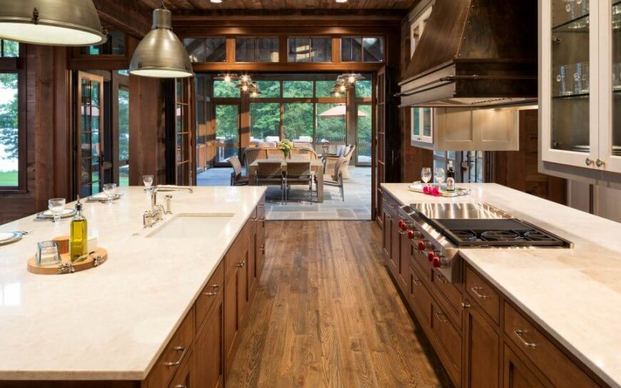 The kitchen features rich wood cabinetry beneath white marble countertops, including the immense island at left with full sink and dining spaces. Through folding doors the space opens up to the enclosed patio room in background.