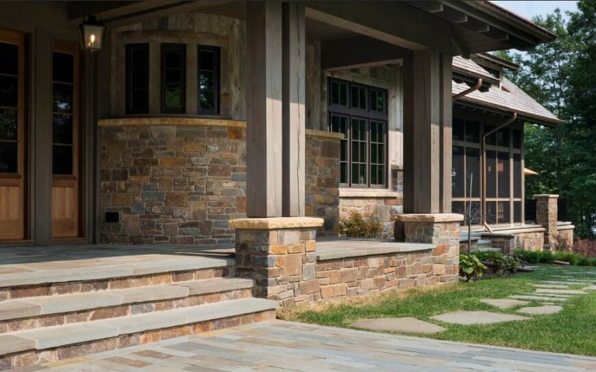 The stone and natural wood construction offers an elemental, solid feel, fitting perfectly within its surroundings. A natural stone path leads from the entrance around the side of the home.