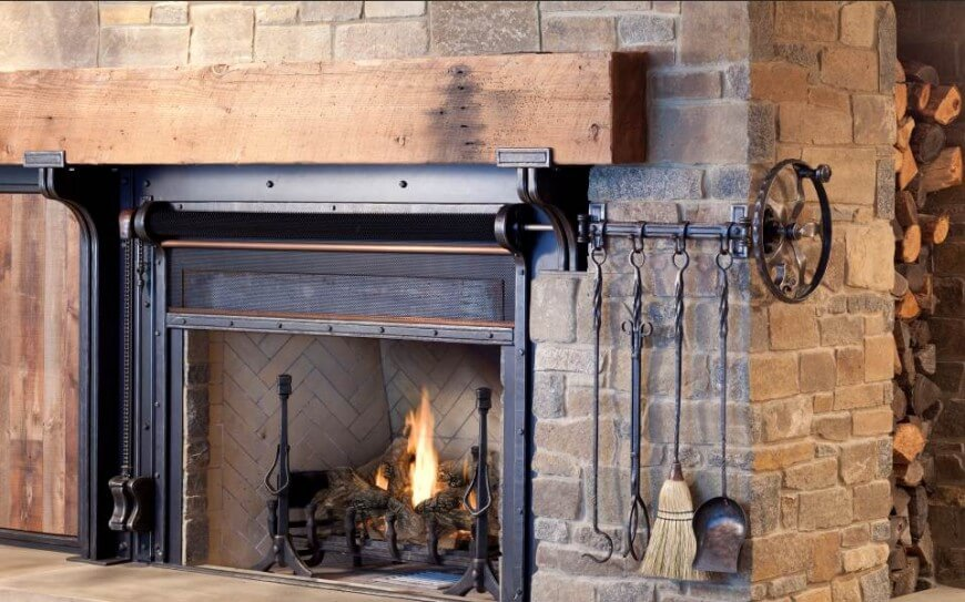 Large stone wrapped fireplace features a retractible screen cover and large natural wood beam mangle, with hidden storage for firewood in back.