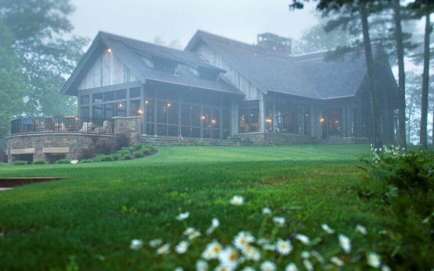 The home fits perfectly with its natural surroundings; seen here in the fog, we see the soft glow of hanging lights inside.
