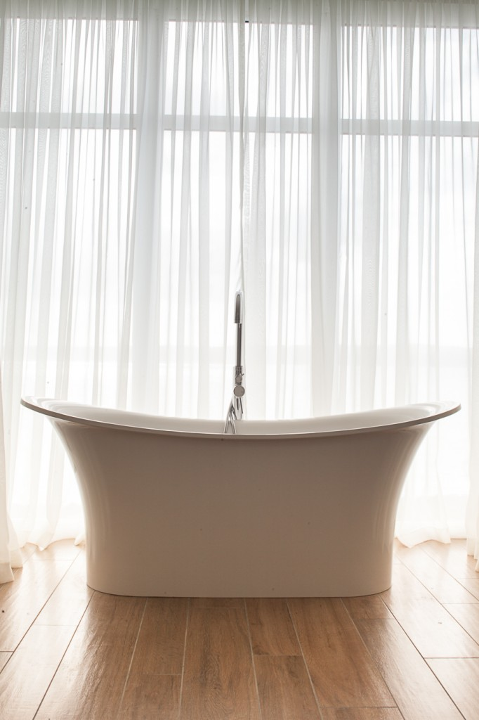 Light hardwood flooring makes another appearance in this bathroom with a large curved soaking tub and airy white curtains.