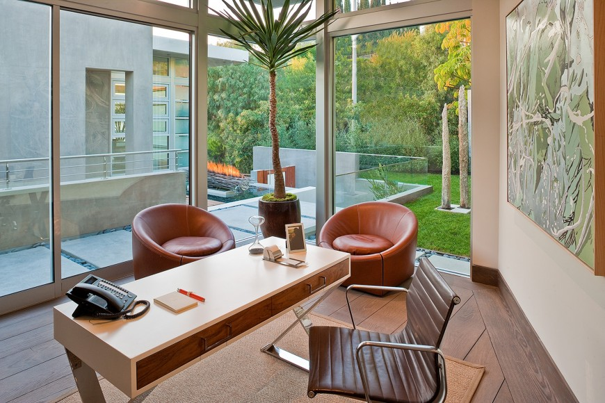 The entry side of the home features this lush corner office, with full view of the water element through full height glass. Minimalist white desk with natural wood drawers stands along with a pair of circular leather chairs at center.