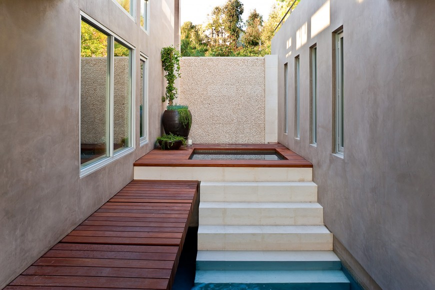 At the end of the pool, we have a raised jacuzzi space with rich wood platform surrounding.