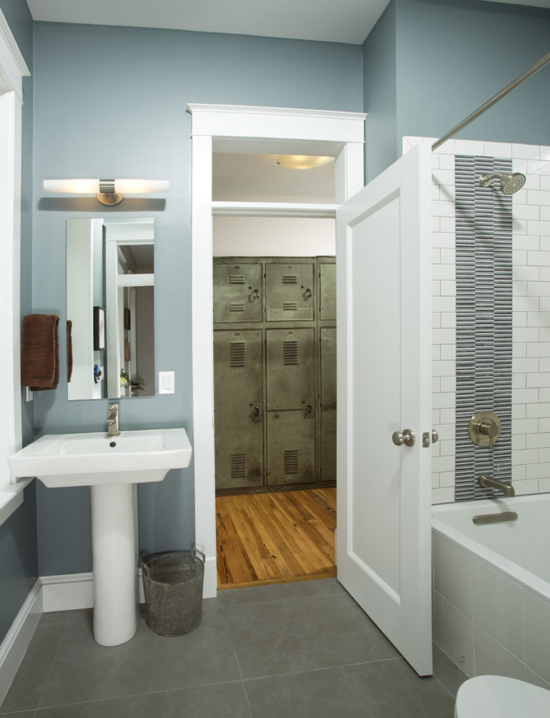 This cool blue and white bathroom has a large soaking tub and shower enclosure on one wall, and a pedestal sink next to the door.