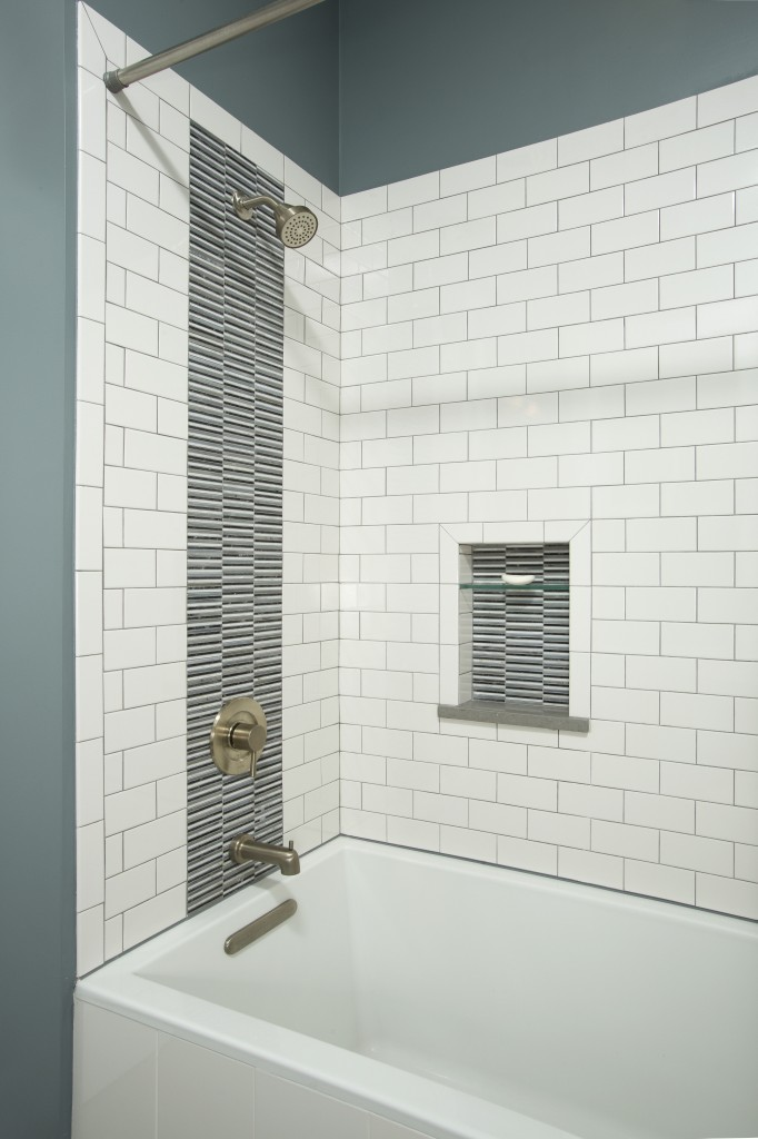 A closer look at the bathtub and shower enclosure shows white subway tiles broked up by black and gray striped tile. The fixtures are brushed nickel.