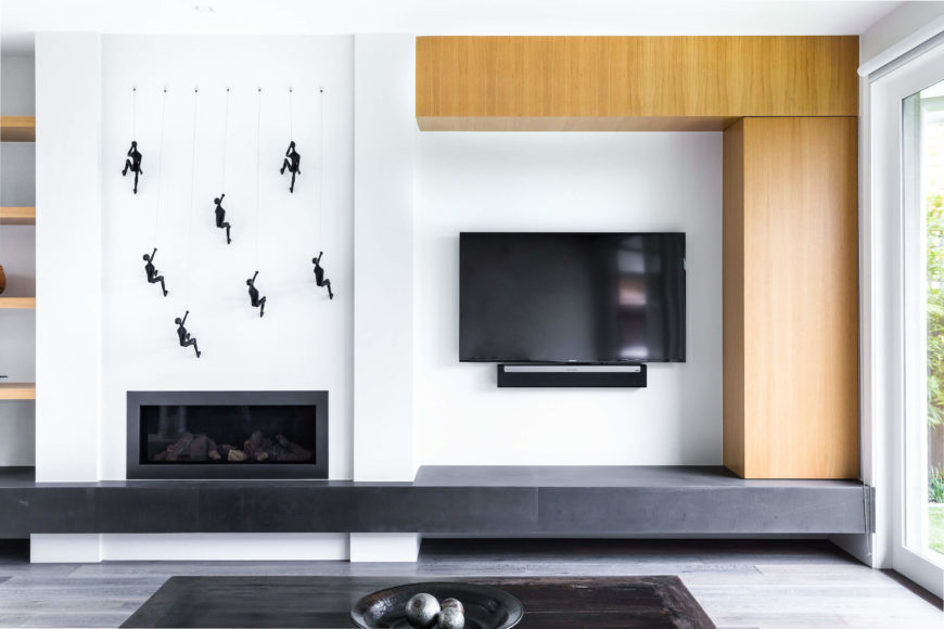 Across the open space, we see the living room area, with a subtle fireplace tucked into the white wall below a set of climbing-man art pieces. Natural wood shelving built into the wall contrasts with stark white and grey tones, while sunlight pours in via full height glass at right.