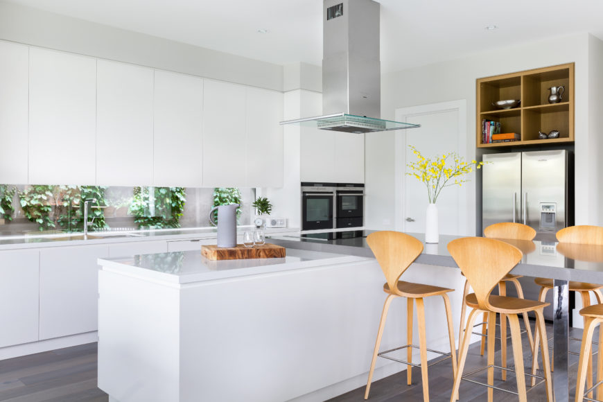 This closer look reveals the silver toned dining table extension on the sleek white island, as well as a windowed backsplash beneath glossy white cabinetry.