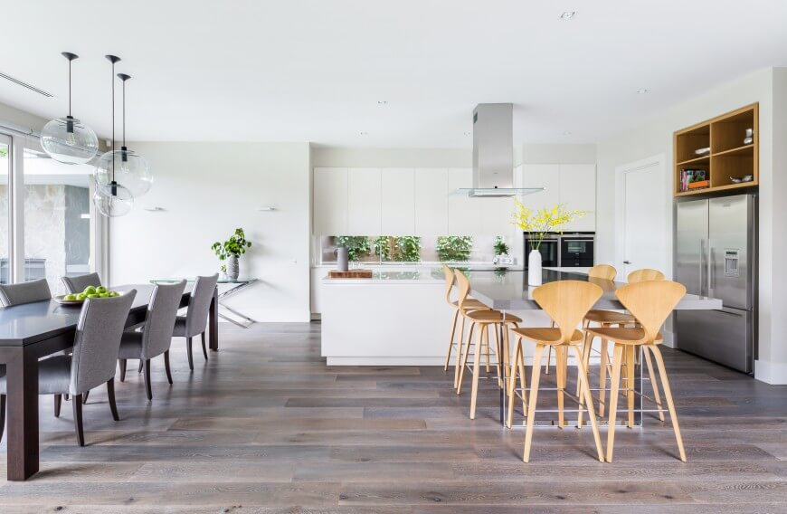 The large central open space holds this innovative kitchen next to a full dining area. White island with cooktop features a lengthy tabletop extension for cozy dinning, as well as stainless appliances and natural wood upper shelving.