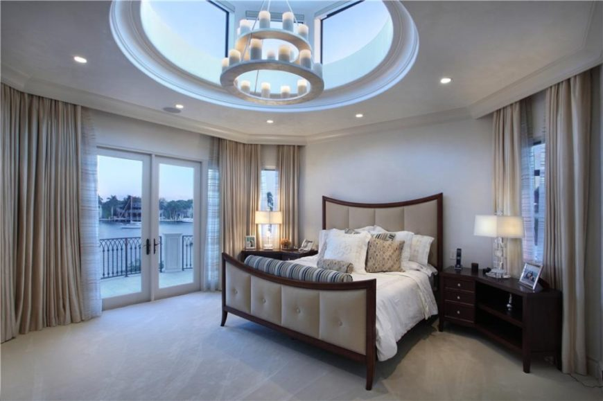 the custom dome ceiling of this elegant master bedroom has a tiered chandelier with electric pillar - Bedroom Balcony Designs