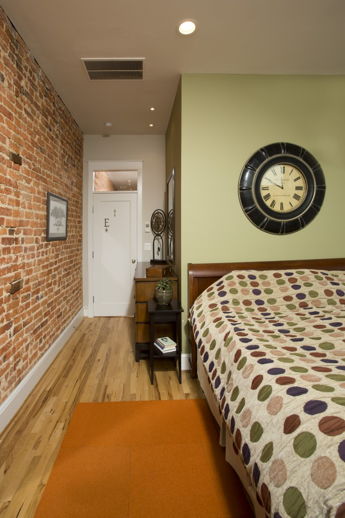 The bedroom displays much of the original features, including the pine flooring and brick wall. The rest of the room is in beige, brown and greens, with dark wood furniture.