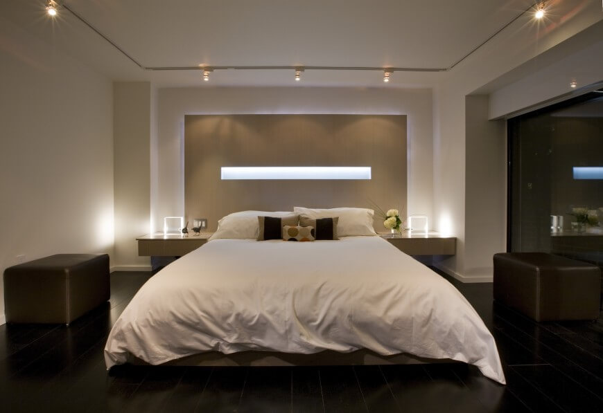 The headboard of this master bedroom is backlit and connects to the nightstands on either side.