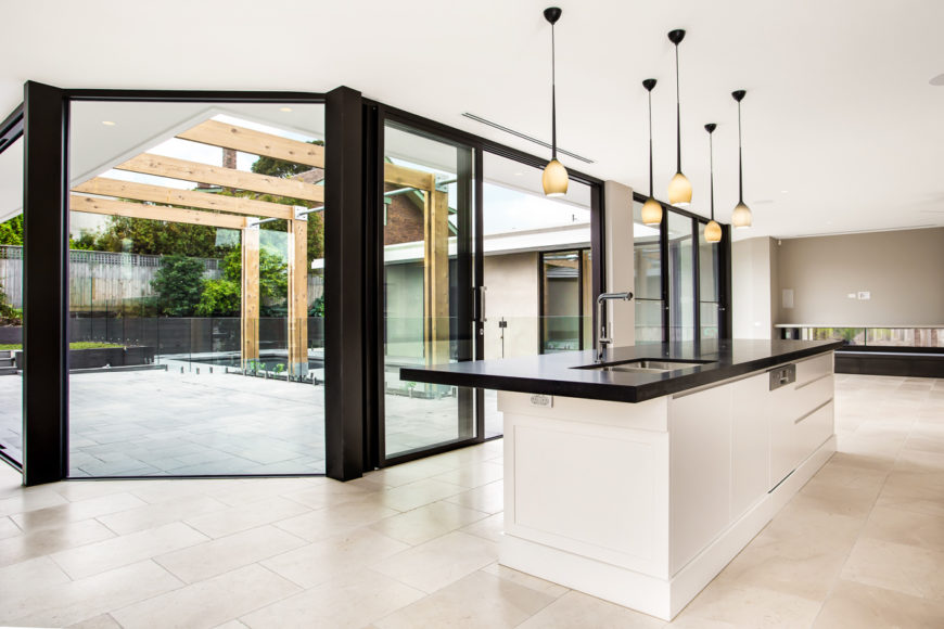 The wide open kitchen and living room space wraps around the new pool and patio area, seen through a bold swath of floor to ceiling glass panels. The large black countertop island seen at right defines the kitchen area.