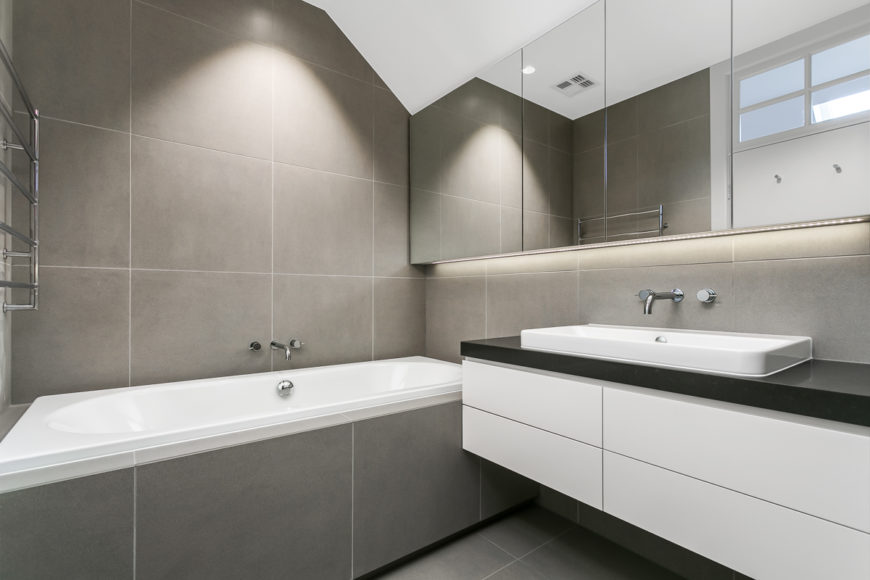 A secondary bathroom features a more subtle mixture of neutral grey tile and white, with an array of seamless mirrors over the floating vanity at right.
