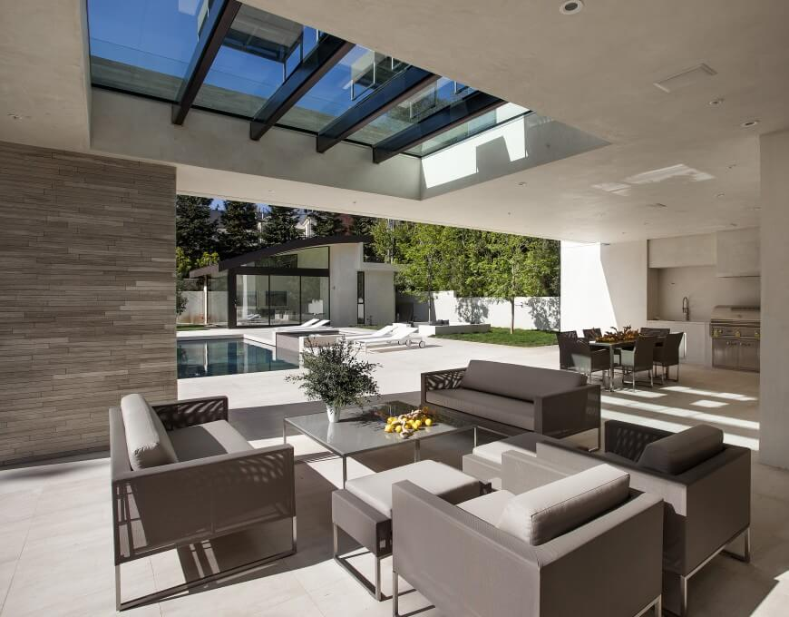 This covered patio has a skylight to keep the space from getting too dark. The patio expands into a dining and outdoor cooking area, and a pool with lounge chairs for sunning. The landscaping is simple, with a few trees and some grass, but the backyard is dominated by the light concrete tiles. Modernity is evident in the simple, clean lines of the furniture.