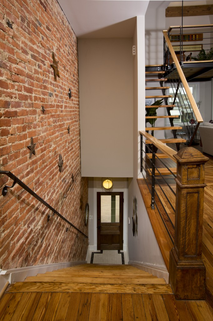 The original pine-heart floors were salvaged, saving both money and original charm. The original brick wall is also exposed on the staircase.