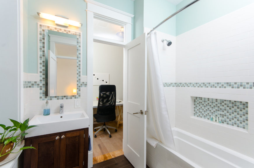 The light flooring leads into dark hardwood flooring in the second bathroom, which matches the dark wood vanity. The shower and tub stall  is white subway tile broken up by a small amount of blue and brown tile in a bar and in a small cubby.