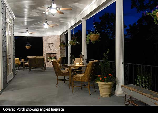 This covered porch has multiple lighted ceiling fans along the white panel ceiling. Multiple seating arrangements and a bench line the wrap-around porch. An unused fireplace is dressed up with a flower box. Hanging baskets line the porch as well.
