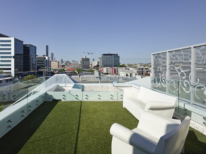 This modern patio is enclosed by glass an industrial-style fencing. The ground is covered with sod and a white sofa and armchair sit upon it. The rooftop patio provides an excellent view of the cityscape. The frosted glass windows behind the furniture have swirling vine patterns.
