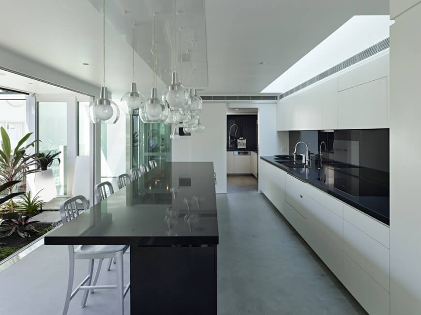 Modern Style Informs The White Cabinetry In This High Contrast Kitchen. Dark Hardwood Flooring Nearly photo - 1