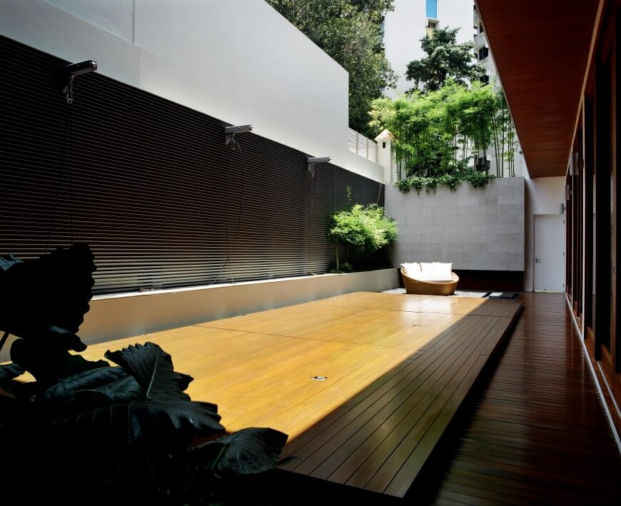 This simple wood patio is between two sections of the home. Part of it is shaded, while the other side is in direct sunlight. A large glass panel on the far side can be blocked off with shades for privacy. A single hanging fern on one side and a large potted plant on the other are the sources of color inside the patio. Large bamboo stalks and moss just peek over the concrete wall.