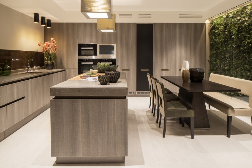 viewed head on the kitchen reveals a large angular dark wood dining table - Kitchens Designers