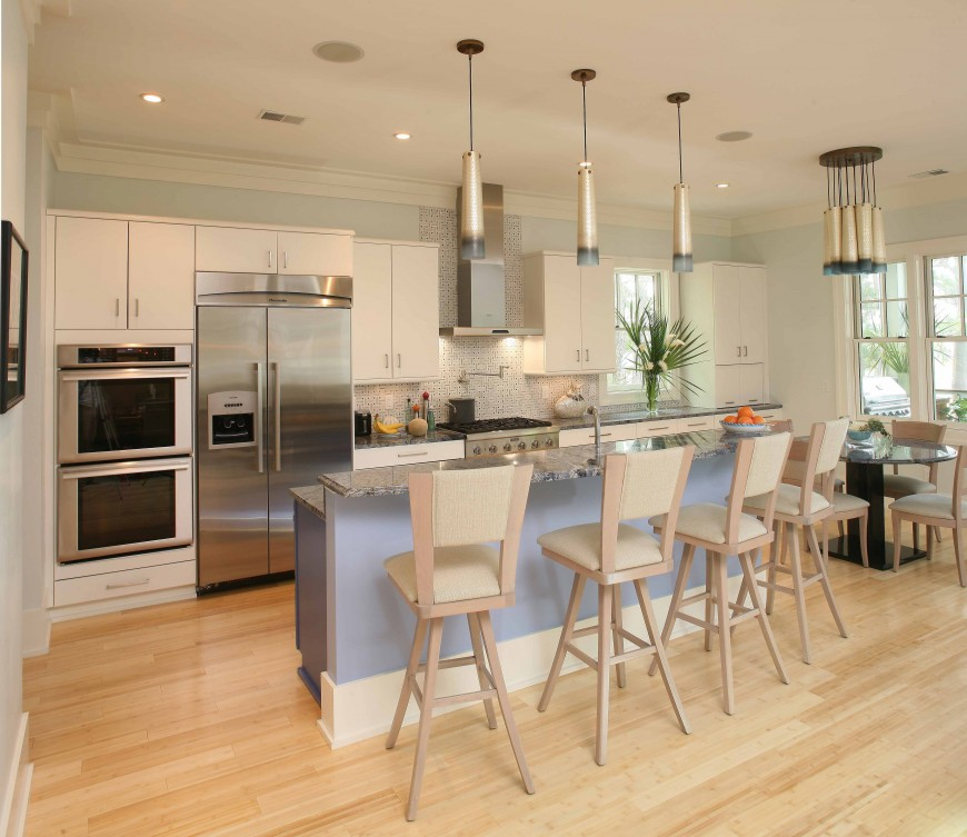 The large open central interior of the home is awash in natural wood and cream tones, splashed with sky blue as seen on the marble topped island here. Stainless steel appliances add contrast, while slender drum pendant lighting adds upper level detail.