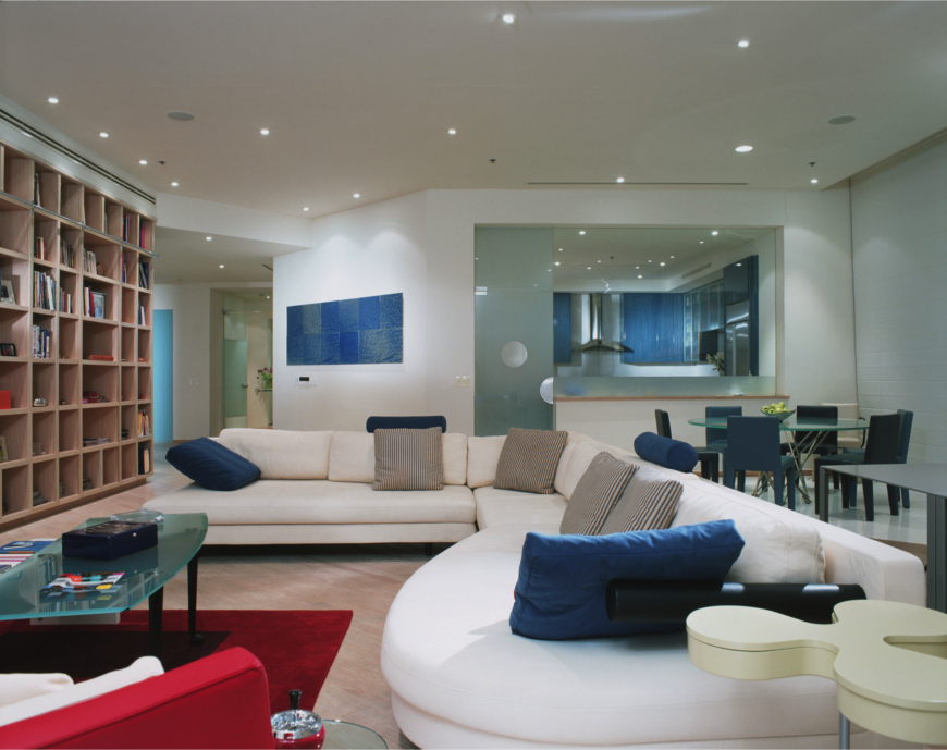The enormous main living area includes a glass dining table, study area, and floor-to-ceiling library wall. The white sectional sofa is spruced up with bright blue accents and primary red rug.