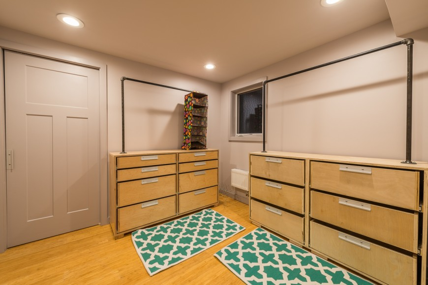 The walk-in closet  is simple, natural wood dressers with pipe used to create a unique place to hang clothing. Two bright rugs bring in a fun pop of color.