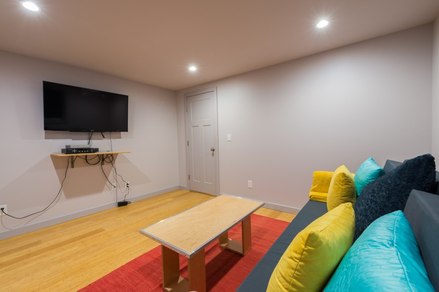 A simple shelf and a wall-mounted television make up the media center. Gray walls keep the attention on the function of the room.