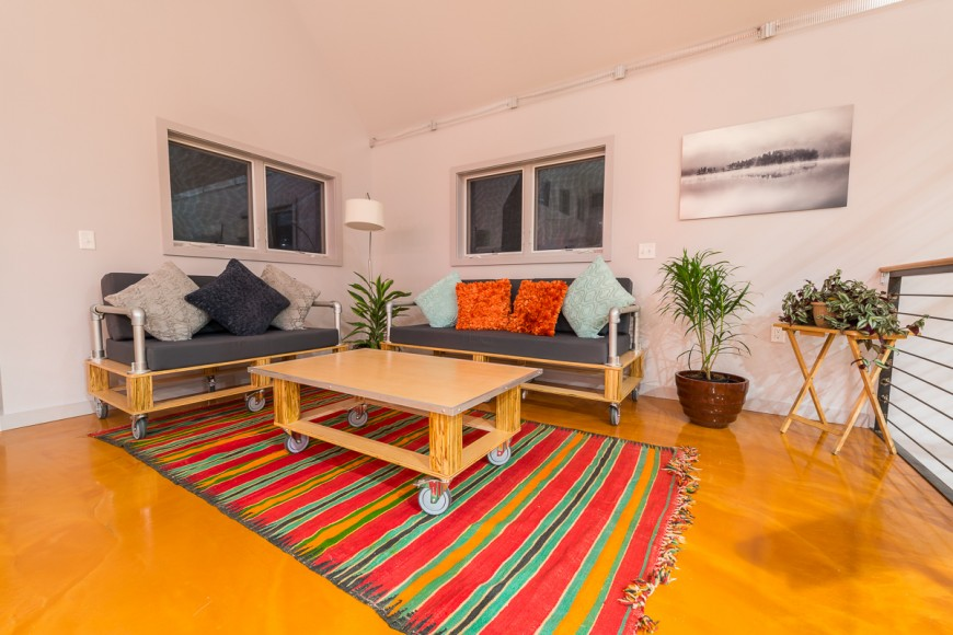 From this lower angle, the brightly colored area rug beneath the love seat and coffee table draws color from both the bright glossy flooring and the accent pillows.