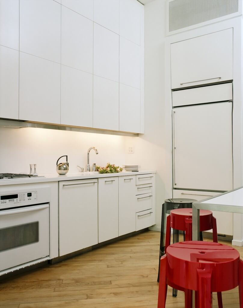 The kitchen is awash in sleek white cabinetry with thin metal hardware. Varying colored stools surround a dining table over more of the light natural hardwood flooring.