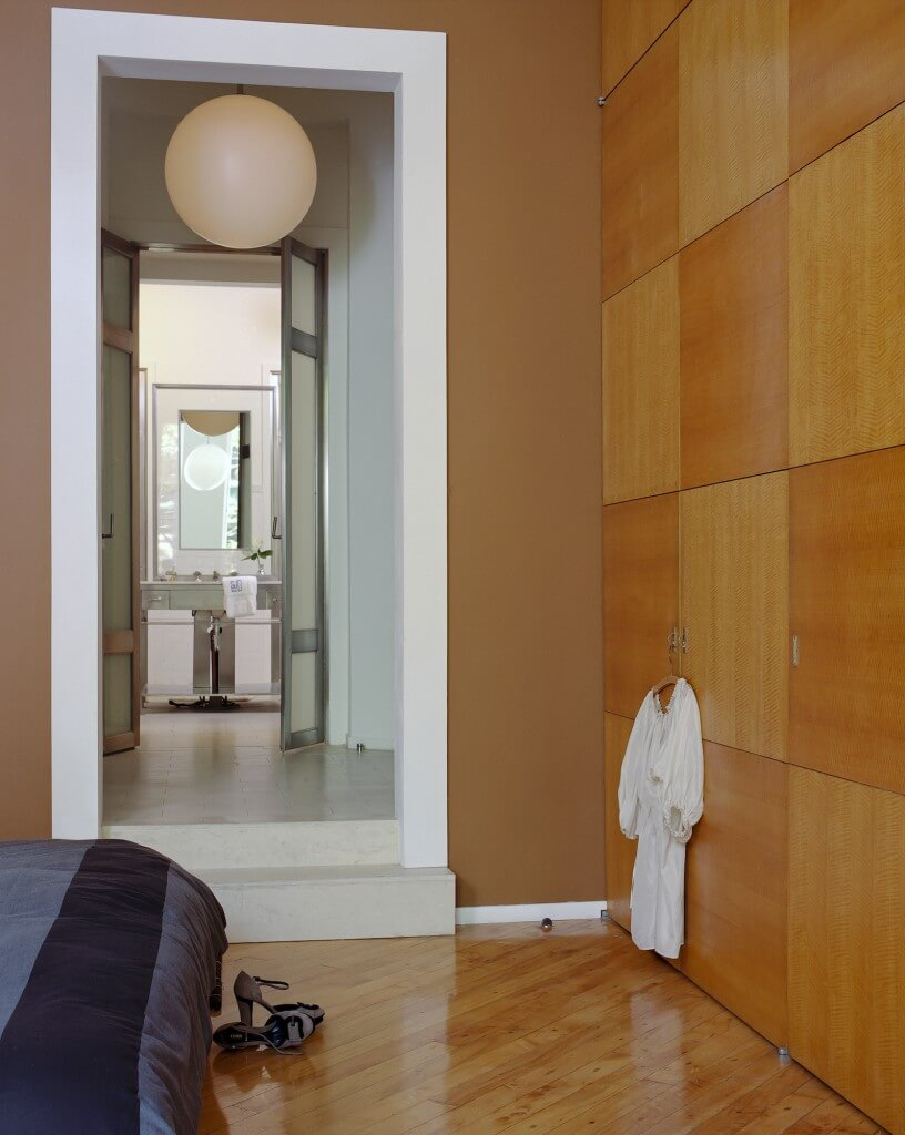The bedroom wall is covered in alternating toned sleek wood cabinetry panels, while a private bath is entered below a spherical chandelier at center.