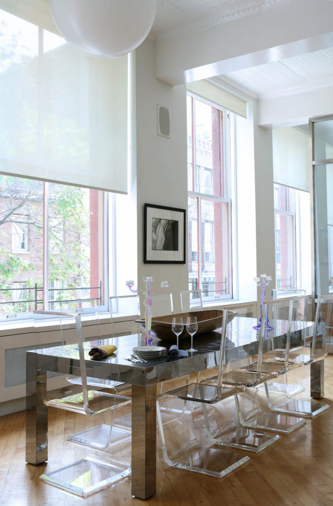 The soaring open space is shared with this ultra-modern dining set, consisting of a mirrored surface dining table and a set of acrylic chairs, making for a crystalline appearance. Massive, full height windows naturally light the space.