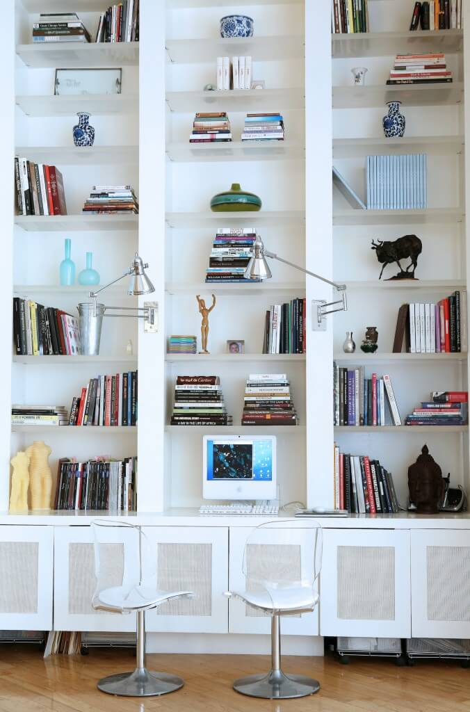 The immense built-in wall shelving offers a desk surface above open-bottom cabinetry, with a pair of moveable sconces for direct lighting. Transparent shelves enhance the open look between thick vertical slabs.