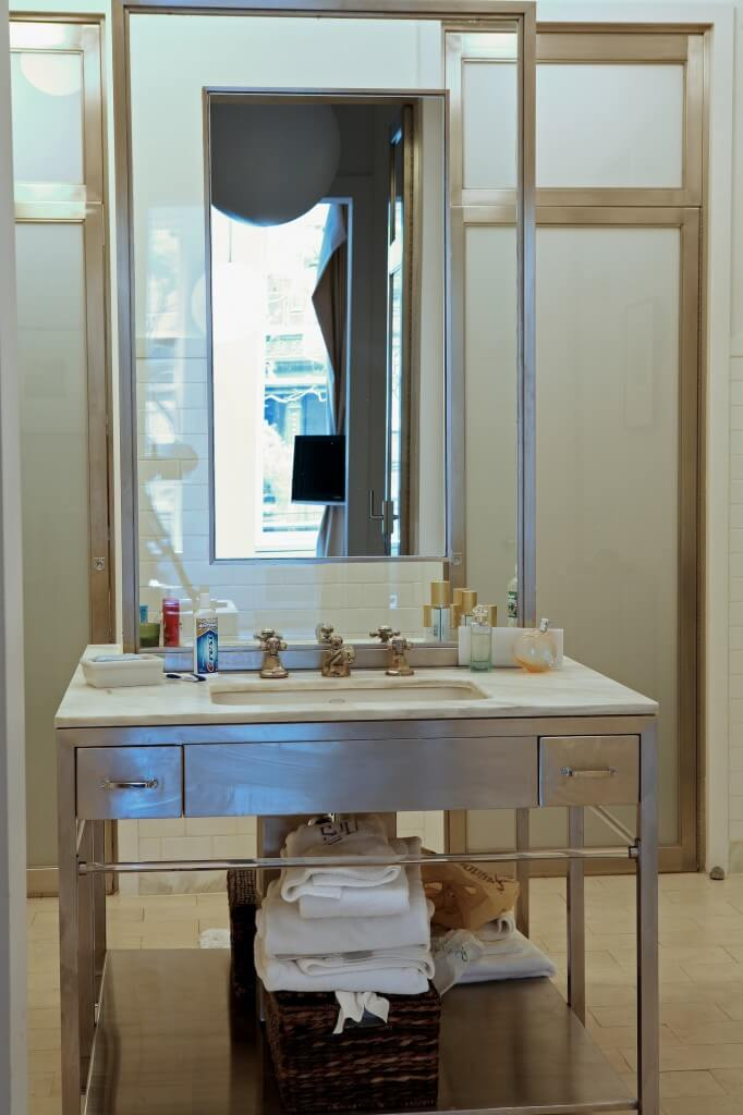 Bathroom features a free standing steel vanity with unique mirror feature, framed in glass. Cream floor tiles match marble countertop.