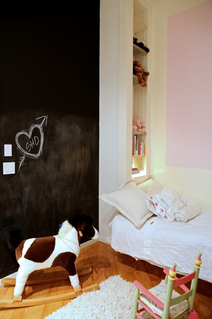 Child's bedroom features an immense chalkboard wall net to built-in shelving at right.