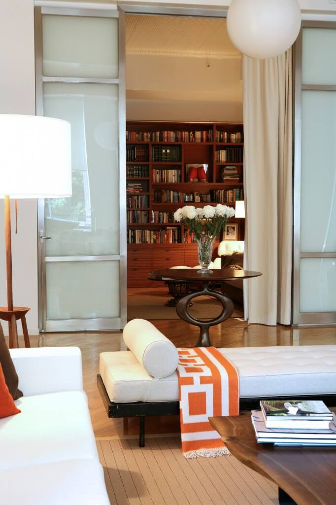 Peering through sliding metal and smoked glass doors toward a smaller office space, we see the seamless expanse of hardwood flooring beneath a wall size natural wood bookcase. The contemporary furniture in this room stands in contrast to the natural hues.
