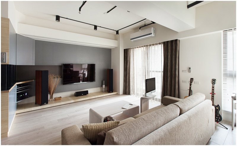 """This view of the main sitting area in the living room in natural sunlight shows the lightly curving open shelving that leads into the back wall. The """"hearth"""" is slightly raised from the floor."""